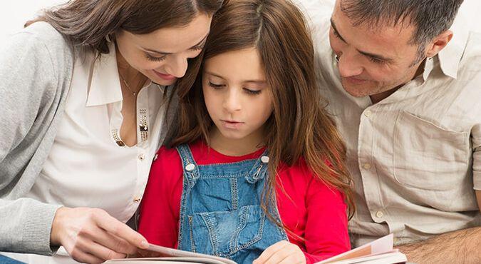 Padres leyendo un libro con su hija